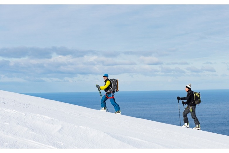 tour skiers ascending with sea view on the background
