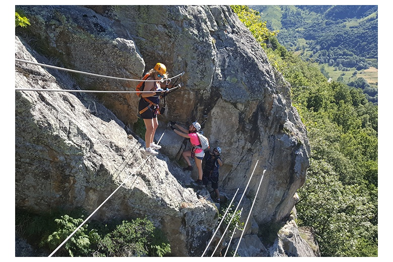 a person crossing the tibetan bridge on the poi d'unha via ferrata and two other about to do it