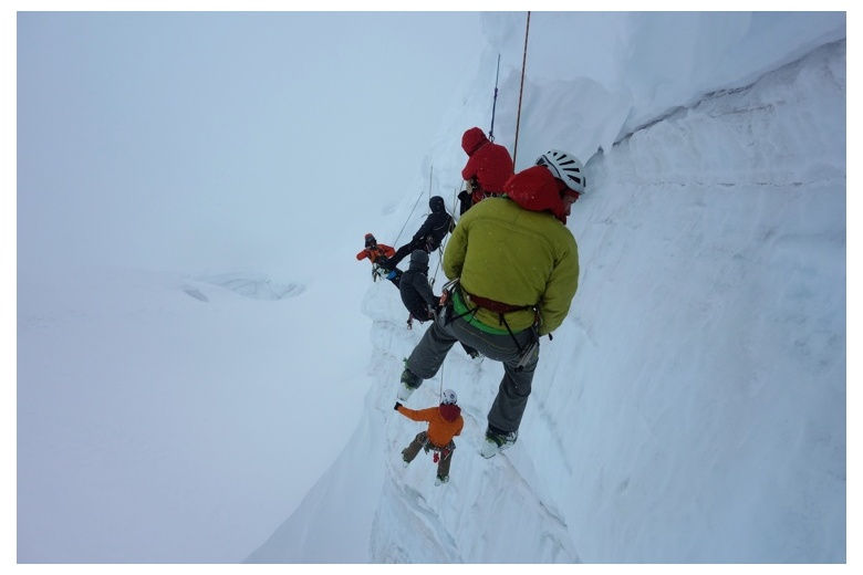 climbers abseiling on an icy and snowy wall