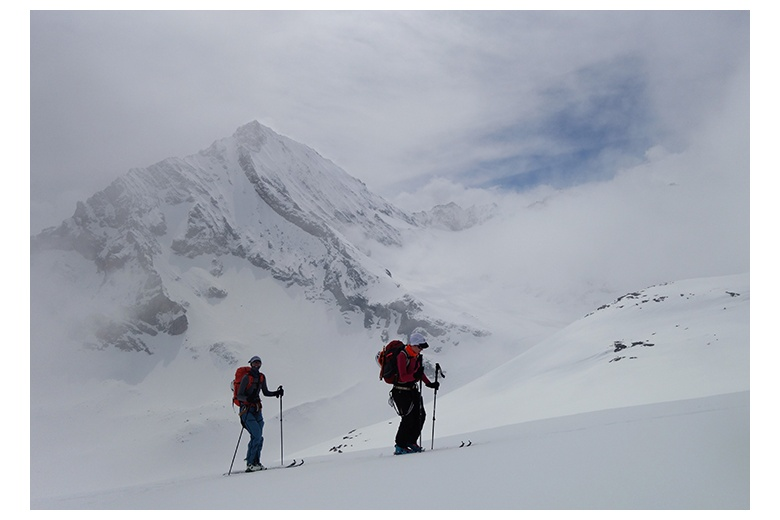 touring skiers ascending with the stunning Dent Parachée at the back of the image.