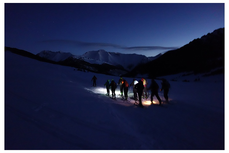 touring skiers at dark with the headlamps on  getting started to climb the tuc de barlonguèra.