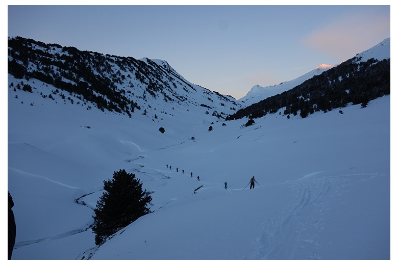 group of touring skiers at valle de parros, first sunlights of the day illuminating the summit of tuc de paaros