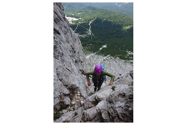 escalando la vía del primo spigolo a la tofana di rozes con vistas preciosas a los bosques y prados verdes de las dolomitas