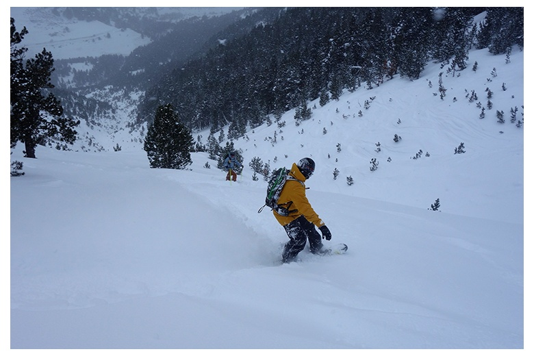 skier and snowboarder taking profit of the fresh snow on the enjoyable descent from dossau to montgarri