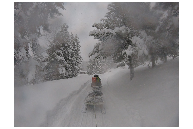 snowmobile dragging skiers through aiguamòg valley in the middle of an intense snow fall