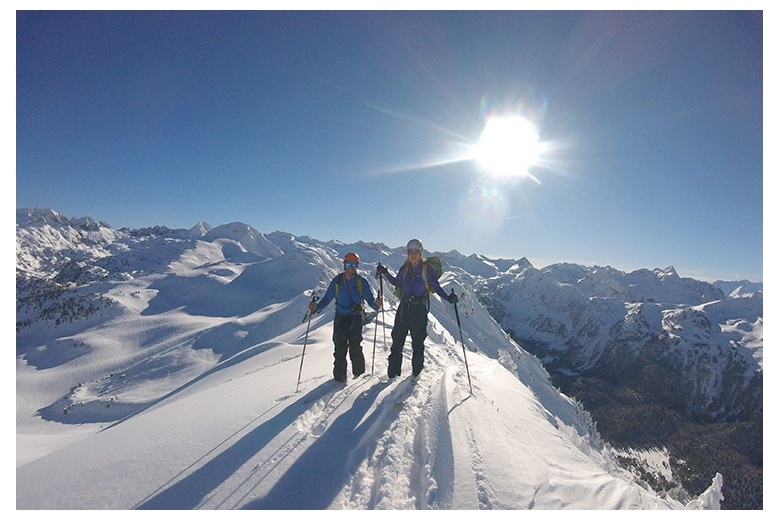 skiers on a superb sunny day on top of the mountain before skiing down on fresh snow