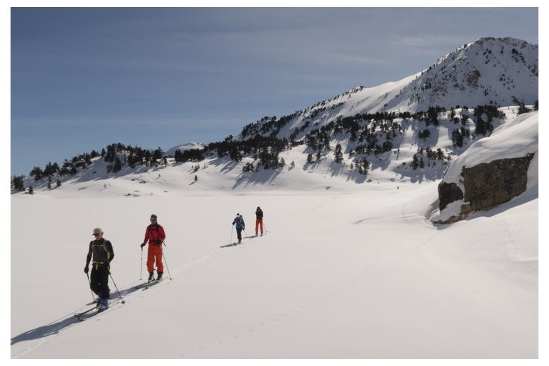 touring skiers crossing a frozen lake