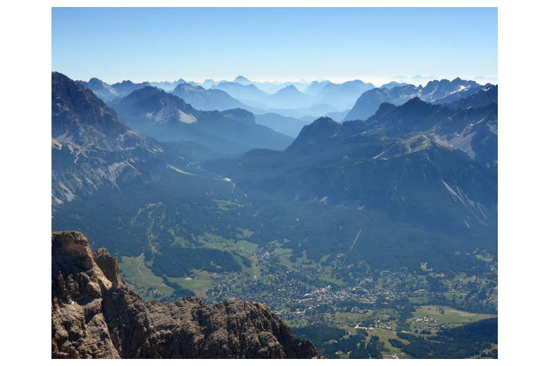 view of a village in dolomites from top of a mountain on a beautiful day