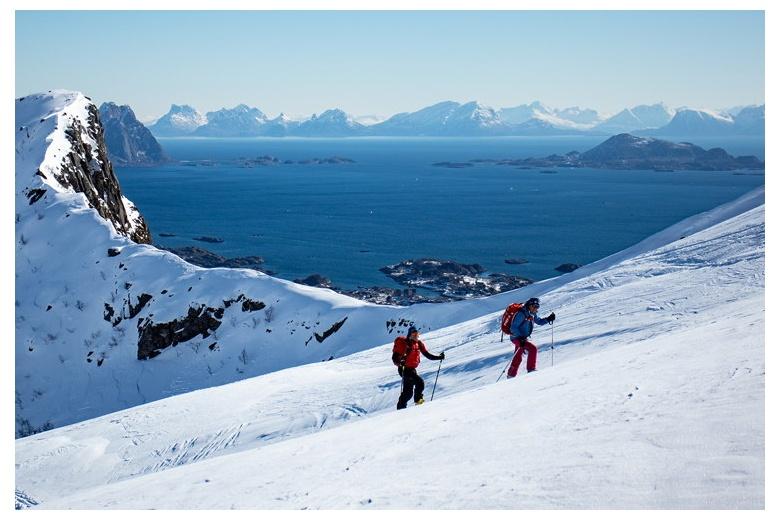 dos esquiadores subiendo con el mar en el fondo en lofoten