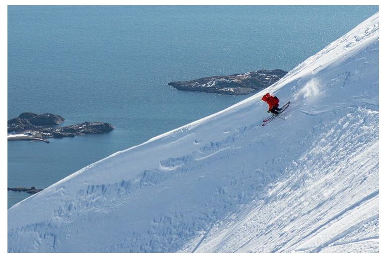 esquiador bajando con el mar en el fondo