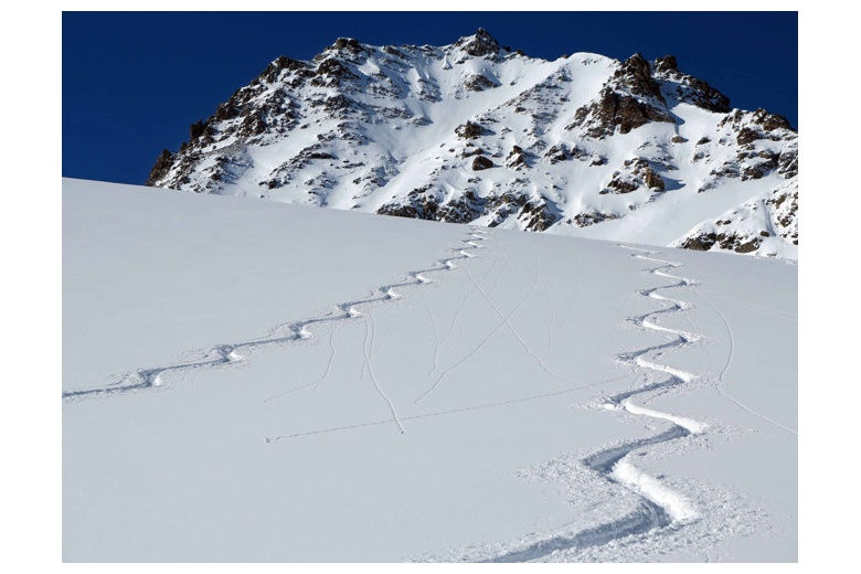 two ski tracks on powder day with mountain on the background