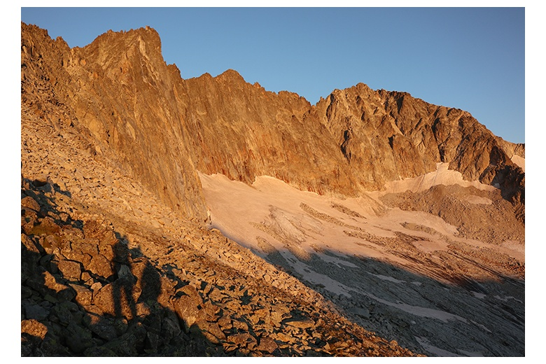 shades of two mountain climbers at sunrise with the view of the salenques-tempestades ridge
