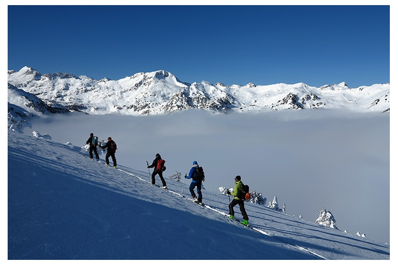 group of touring skiers in la peülla with an incredible sea of clouds and summits above it as a view