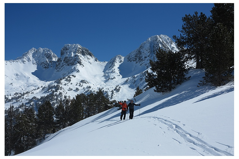 mountaineering skiers touring towards the saboredo hut with the astonishing pic de locampo at the back