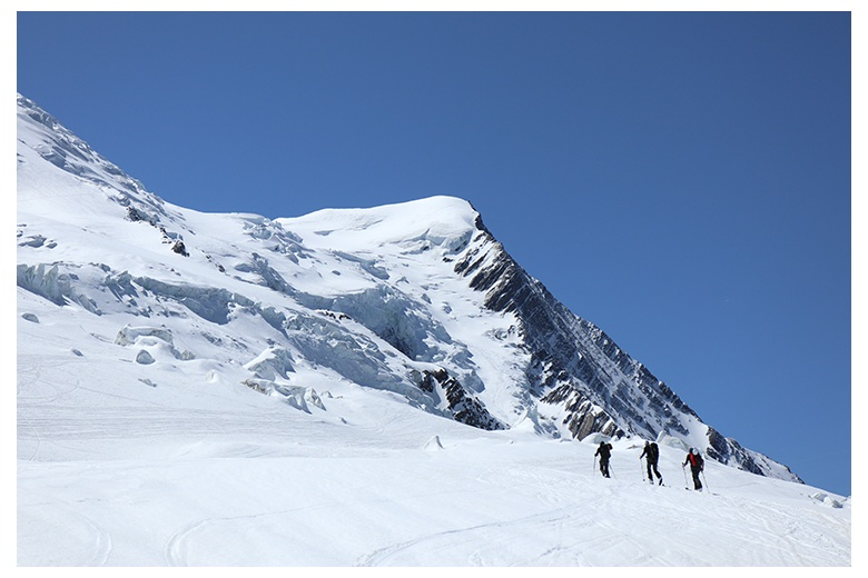 group of touring skiers skinning up the mont blanc on blue sky day