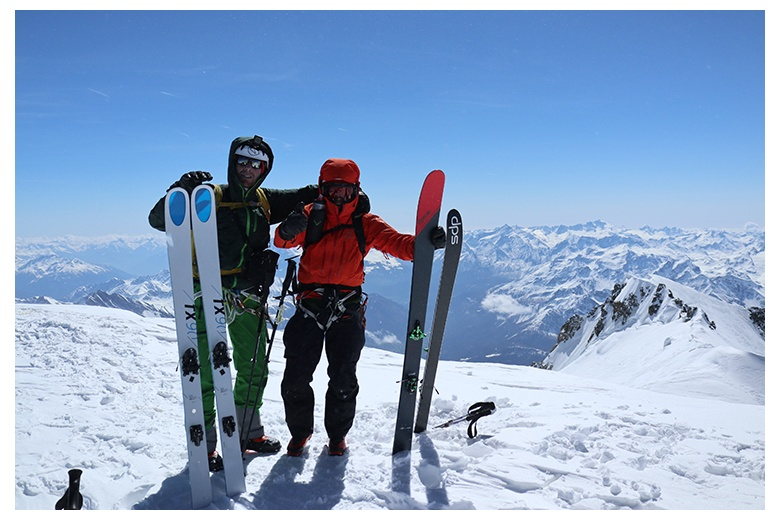 victorious ski climbers on mont blanc summit with one of the astonishing panoramic views at their back
