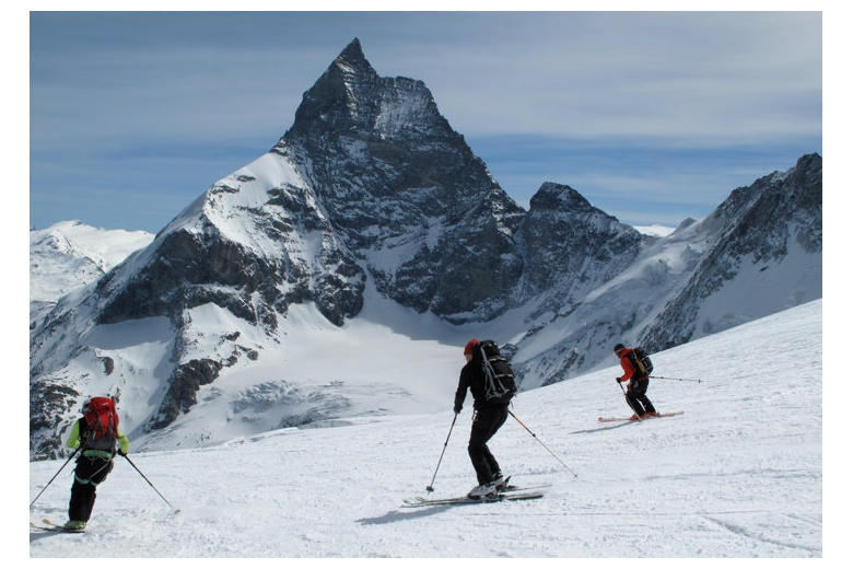 group of people skiing down to zermatt with Matterhorn on the background