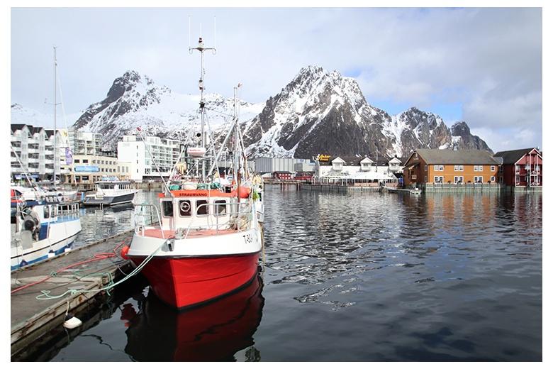 barco pesquero amarrado en pueblo de las islas lofoten. montañas escarpadas en contraste al fondo de la imagen.