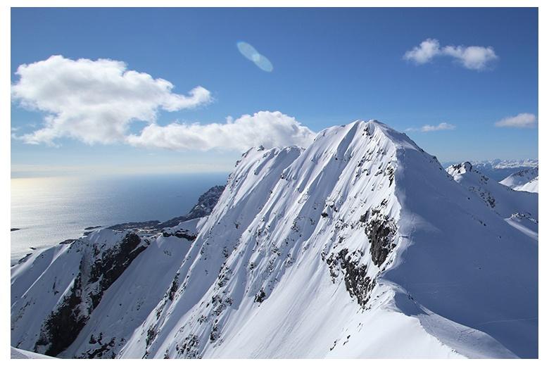 vista preciosa de montaña escarpada con el mar al fondo y cielo azul pincelado por alguna nube