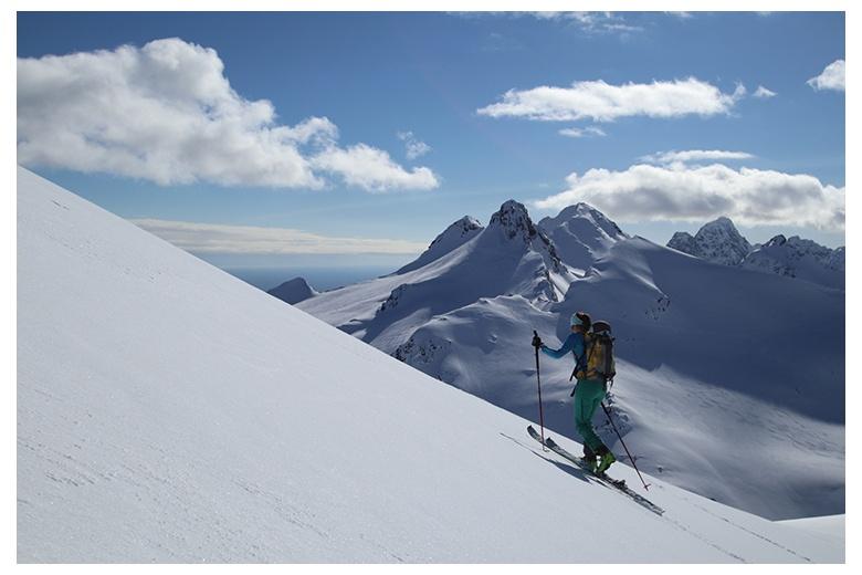 esquiadora de montaña ascendiendo en las islas lofoten con un día insuperable equiparable a las impresionantes vistas de mar y cimas