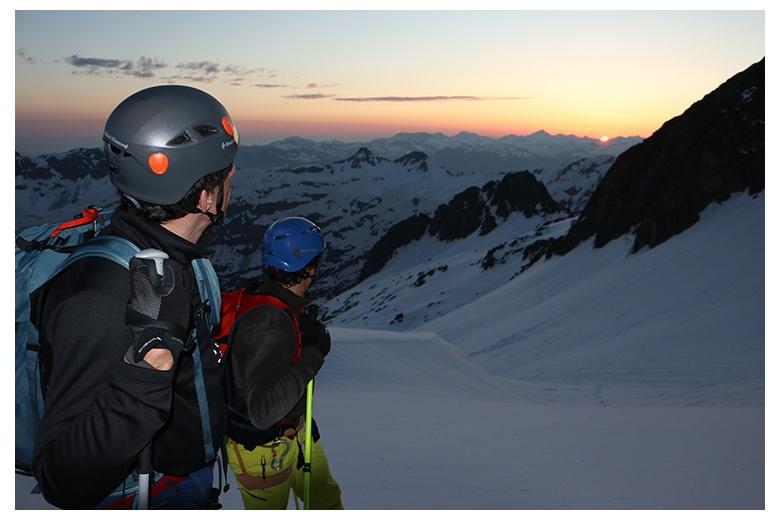 2 esquiadores de montaña admiran la salida del sol en el macizo de la maladeta de camino a la cima del Aneto
