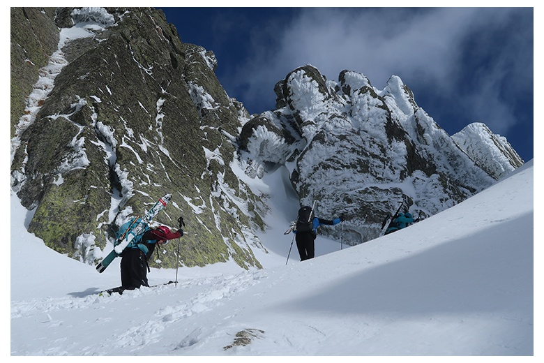 two mountaineering skiers getting past the bretxa de pauss at serra de tumeneia