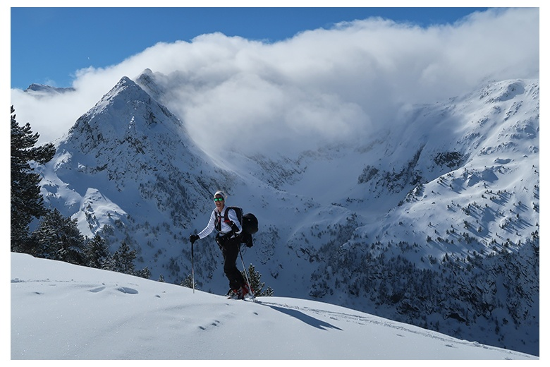 tour skier ascending towards the tuc de salana summit with the montardo on the background hidden behind the clouds