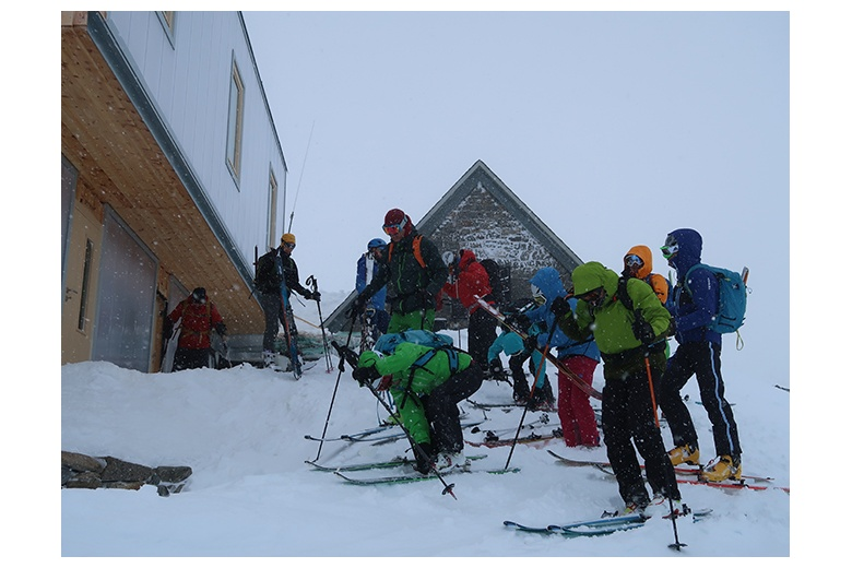group of mountaineering skiers getting ready for the action of the day leaving the refugi joan ventosa i calvell