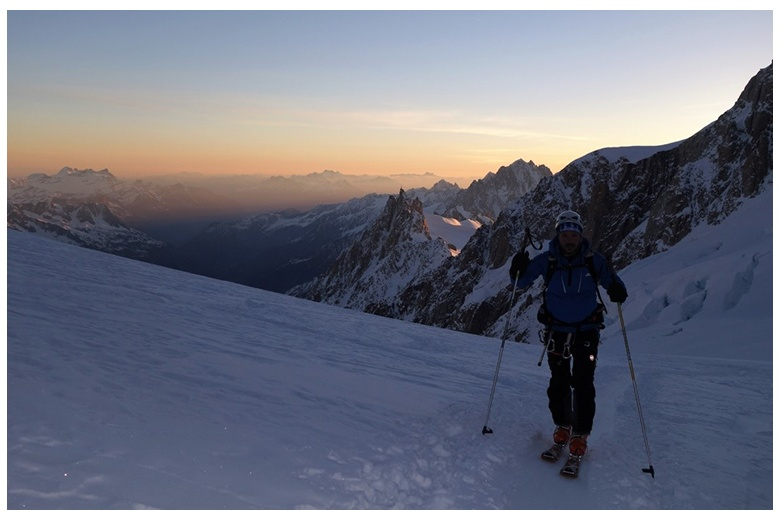 ski tourer at sunrise leaving behing the grands mulets hut on his way to the top of mont blanc