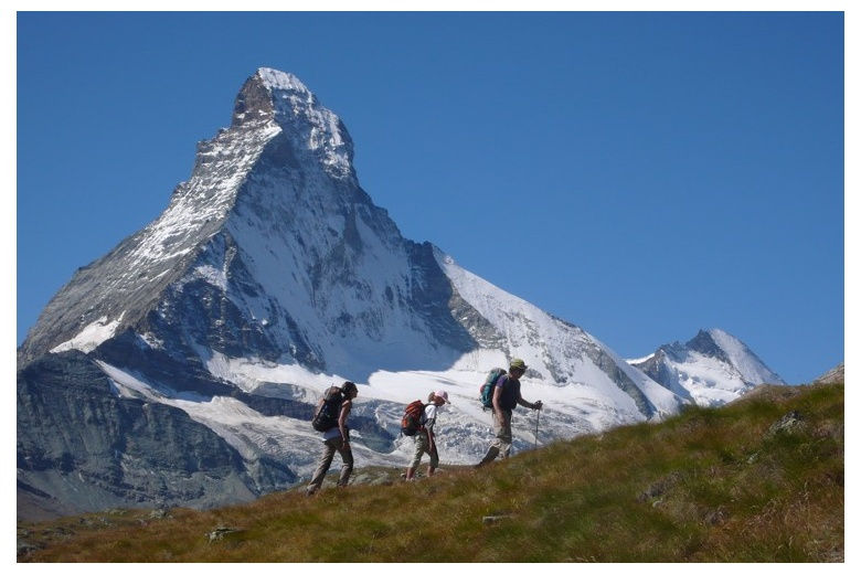 hikers on an up-slope with the unique matterhorn on the background