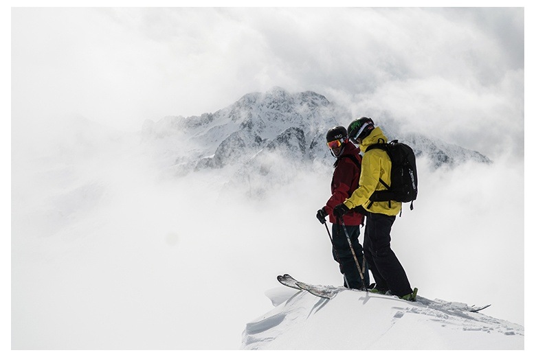 image of two skiers on a ledge just about to jump off with the Punta Alta on the background surrounded by clouds