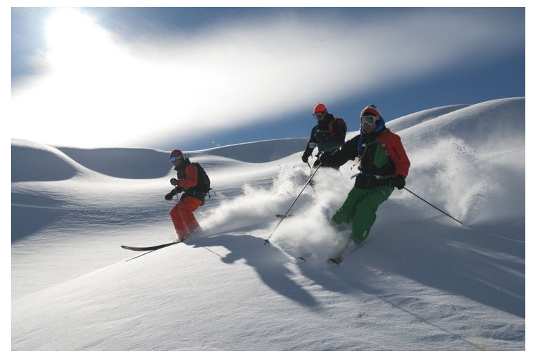 group of three people skiing down off piste run in baqueira-beret