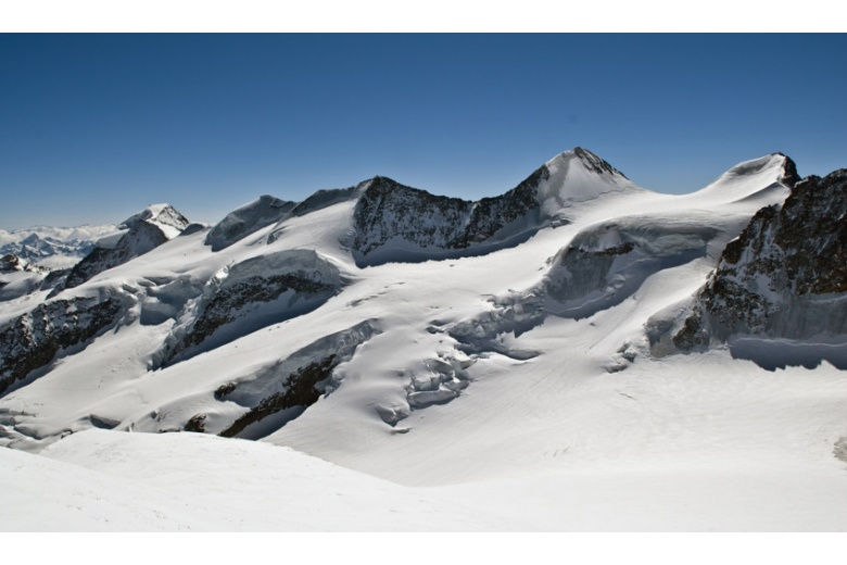 panoramic view of several mountain peaks  covered by snow, plus impressive seracs