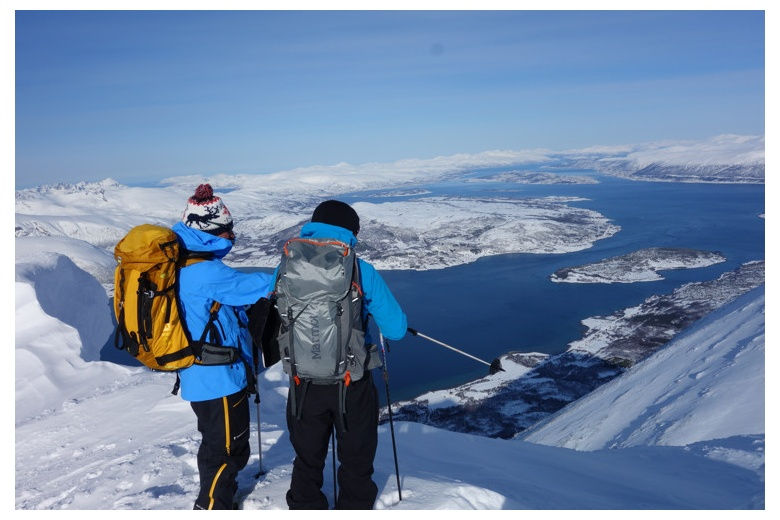 skiers contemplating the view of Tromso from top of mountain