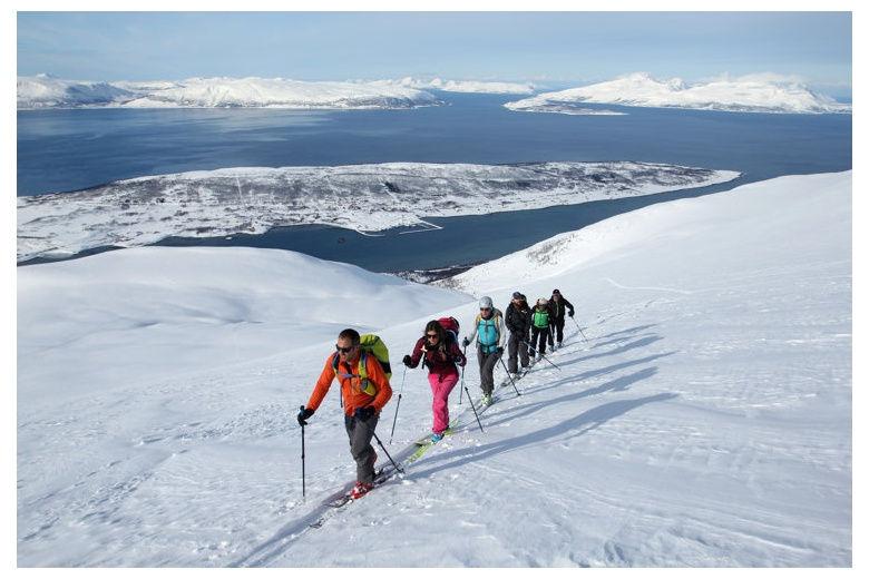 grupo esqui de montaña subiendo el lyngen con el mar en el fondo