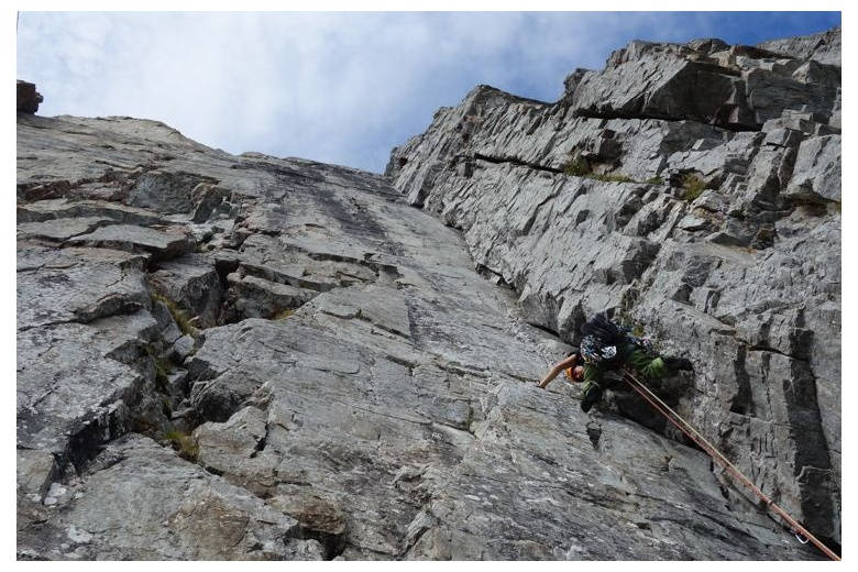 climber progressing on a beautiful dihedron at the alps
