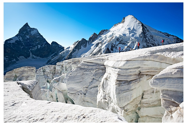 group of people close to a huge crevasse on stockji glacier with dent d'hérens and matterhorn at the back