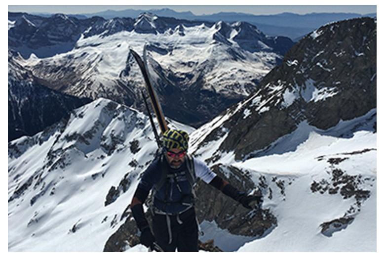 esquiador alcanzando la cima por la arista con esquís a la espalda